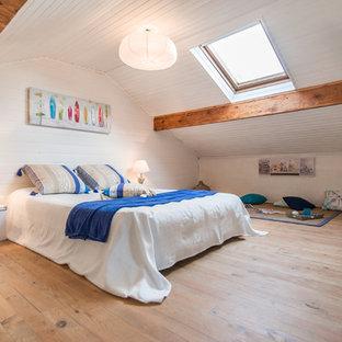 Inspiration pour une chambre marine avec un mur blanc et un sol en bois clair.
