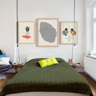 Cette image montre une chambre parentale nordique de taille moyenne avec un sol en bois foncé et un mur blanc.