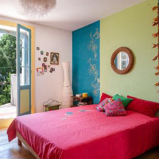 Diseño de dormitorio bohemio con paredes azules, suelo de madera en tonos medios y suelo marrón