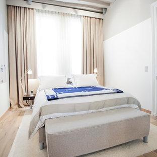 Exemple d'une grand chambre parentale tendance avec un mur blanc et un sol en bois clair.