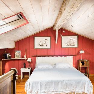 Lantlig inredning av ett sovrum, med röda väggar, mellanmörkt trägolv och brunt golv