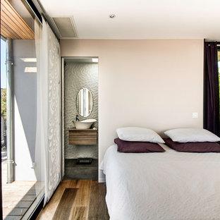 Exemple d'une chambre tendance avec un mur blanc et un sol en bois brun.