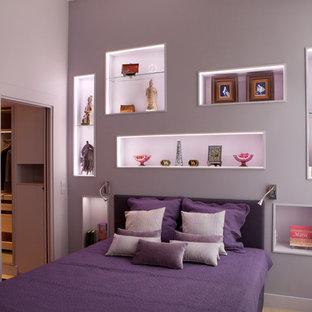 Cette photo montre une grande chambre parentale tendance avec un mur violet, un sol en bois clair, aucune cheminée et un sol marron.