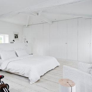 Réalisation d'une chambre nordique avec un mur blanc et un sol en bois peint.