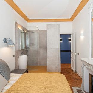 Cette photo montre une chambre parentale tendance de taille moyenne avec un mur blanc, un sol en bois brun et une cheminée standard.