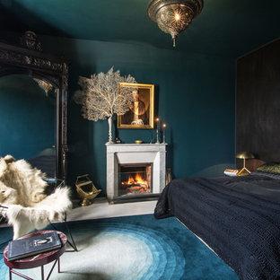 Modelo de dormitorio bohemio con paredes azules, suelo de madera pintada, chimenea tradicional, marco de chimenea de piedra y suelo blanco