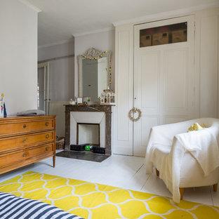 Réalisation d'une chambre parentale nordique de taille moyenne avec un mur blanc, un sol en bois peint, une cheminée standard et un manteau de cheminée en pierre.