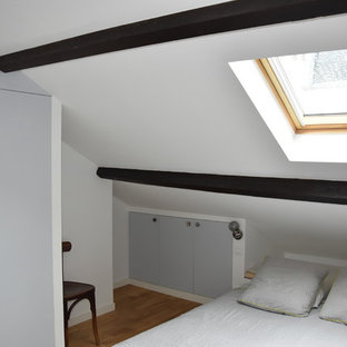 Inspiration for a small midcentury loft-style bedroom in Paris with white walls and light hardwood floors.