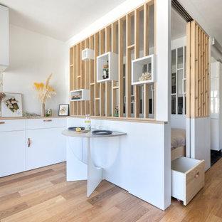 Modelo de dormitorio principal, contemporáneo, pequeño, con paredes blancas y suelo de contrachapado