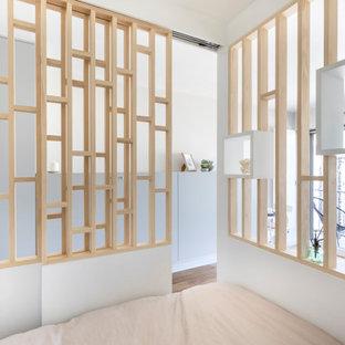 Ispirazione per una piccola camera matrimoniale minimal con pareti bianche e pavimento in compensato