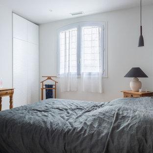 Réalisation d'une chambre parentale design avec un mur blanc.