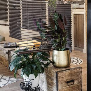 Modelo de dormitorio tropical con paredes grises, suelo laminado y suelo beige
