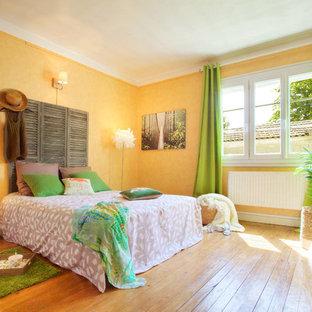 Idée de décoration pour une chambre parentale champêtre de taille moyenne avec un mur jaune et un sol en bois clair.