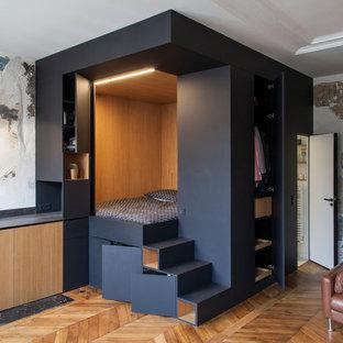 Cette image montre une petit chambre parentale design avec un mur noir, un sol en bois foncé et aucune cheminée.
