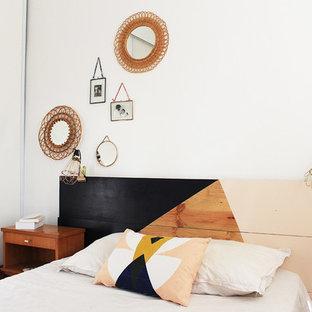 Idées déco pour une chambre adulte éclectique avec un mur blanc, un sol en bois clair et aucune cheminée.