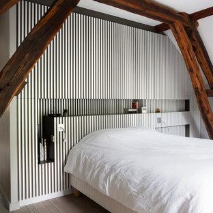 Idée de décoration pour une petite chambre design avec un mur gris, un sol en bois clair et aucune cheminée.