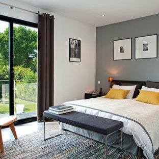 Exemple d'une chambre parentale tendance de taille moyenne avec un mur gris.