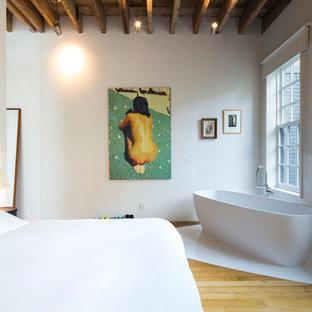 Cette photo montre une grand chambre parentale tendance avec un mur blanc et un sol en bois clair.