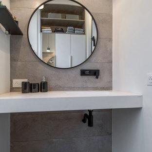 Modelo de dormitorio principal, minimalista, pequeño, con paredes grises, suelo de baldosas de cerámica y suelo gris