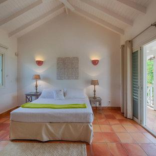 Idée de décoration pour une chambre méditerranéenne avec un mur blanc, un sol en carreau de terre cuite et un sol orange.