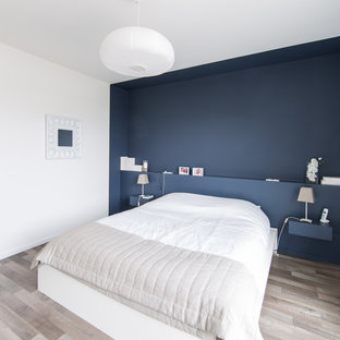 Foto på ett mellanstort funkis huvudsovrum, med blå väggar och ljust trägolv