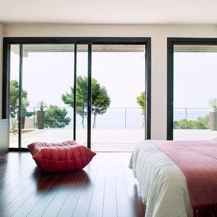 Idée de décoration pour une grande chambre parentale design avec un mur blanc et un sol en bois foncé.