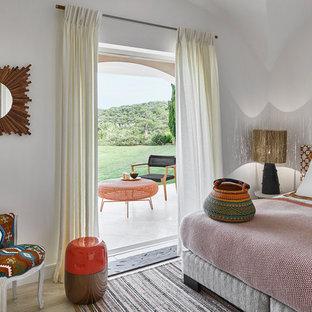 Imagen de dormitorio costero, de tamaño medio, con paredes blancas, suelo de travertino y suelo beige