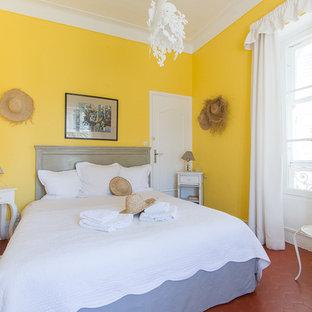 На фото: большая гостевая спальня в средиземноморском стиле с желтыми стенами и полом из терракотовой плитки с