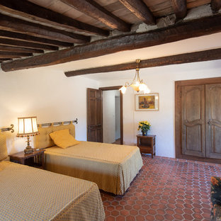 Photo of a mediterranean bedroom in Nice with white walls, terra-cotta floors and red floor.