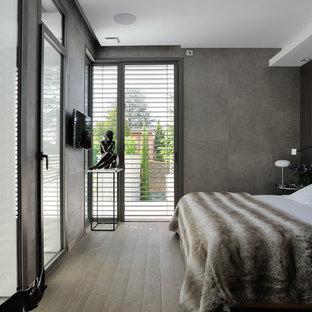 Cette photo montre une chambre parentale tendance de taille moyenne avec un mur gris et un sol en bois brun.