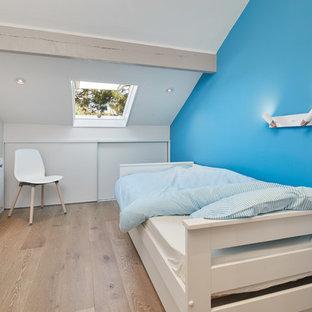 Idées déco pour une chambre bord de mer avec un mur bleu, un sol en bois brun et un sol marron.