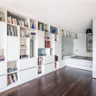 Exemple d'une grande chambre tendance avec un mur blanc et un sol en bois foncé.