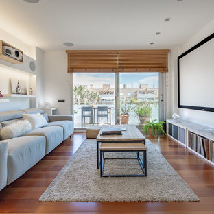 Mid-sized danish open concept medium tone wood floor and brown floor home theater photo in Barcelona with white walls and a projector screen