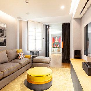 Imagen de cine en casa cerrado, contemporáneo, con paredes grises, suelo de madera en tonos medios y pantalla de proyección