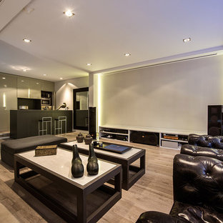 Large modern open concept home theatre in Madrid with white walls, medium hardwood floors and a projector screen.