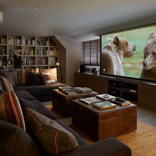 Modelo de cine en casa cerrado, contemporáneo, grande, con pantalla de proyección y paredes grises