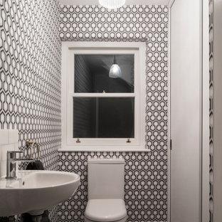 Foto di un bagno di servizio minimal con WC monopezzo, pareti nere, lavabo sospeso, pavimento grigio e top bianco