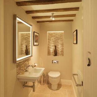 Photo of a small rural cloakroom in Hampshire with a wall-mounted sink, beige walls, a one-piece toilet, beige tiles, glass tiles and limestone flooring.