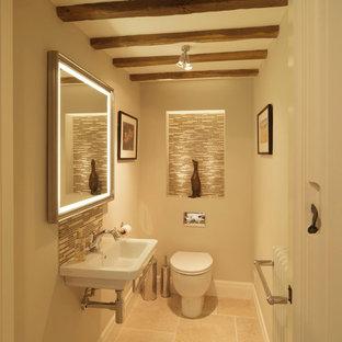 Esempio di un piccolo bagno di servizio country con lavabo sospeso, pareti beige, WC monopezzo, piastrelle beige, piastrelle di vetro e pavimento in pietra calcarea