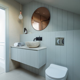 This is an example of a medium sized scandinavian cloakroom in London with flat-panel cabinets, blue cabinets, a wall mounted toilet, blue walls, a vessel sink, grey floors and white worktops.