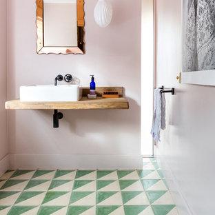 Idée de décoration pour un grand WC et toilettes bohème avec un mur rose, un sol en carreaux de ciment, un lavabo suspendu, un plan de toilette en bois, un sol vert et un plan de toilette marron.