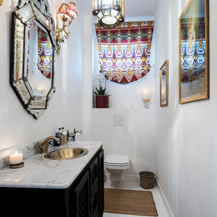 Inspiration for a mediterranean cloakroom in London with freestanding cabinets, black cabinets, a wall mounted toilet, white walls and a built-in sink.