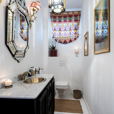 Inspiration for a mediterranean powder room remodel in London with furniture-like cabinets, black cabinets, a wall-mount toilet, white walls and a drop-in sink