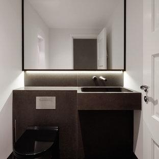 Immagine di un bagno di servizio contemporaneo di medie dimensioni con WC sospeso, piastrelle nere, piastrelle di pietra calcarea, pareti nere, pavimento in pietra calcarea, lavabo integrato, top in pietra calcarea e pavimento nero