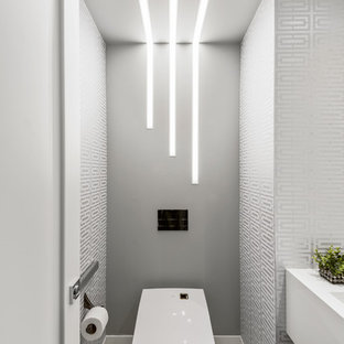 Design ideas for a contemporary cloakroom in West Midlands with a wall mounted toilet, porcelain flooring, white worktops, multi-coloured walls and white floors.