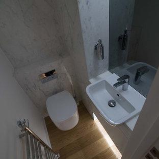 Foto di un piccolo bagno di servizio minimal con ante lisce, ante bianche, WC sospeso, lastra di pietra, parquet chiaro, lavabo da incasso, top in marmo e piastrelle bianche