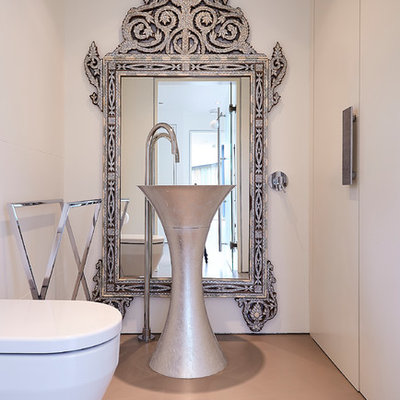 Inspiration for a mid-sized mediterranean orange floor powder room remodel in London with flat-panel cabinets, white cabinets, a wall-mount toilet and white walls