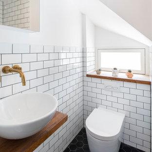 Kleine Nordische Gästetoilette mit weißen Fliesen, Metrofliesen, weißer Wandfarbe, Aufsatzwaschbecken, Waschtisch aus Holz, schwarzem Boden, brauner Waschtischplatte und Wandtoilette in London