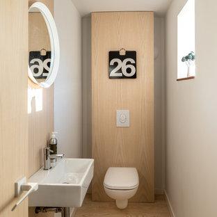 На фото: туалеты в скандинавском стиле с инсталляцией, белыми стенами, паркетным полом среднего тона, подвесной раковиной, коричневым полом и белой столешницей