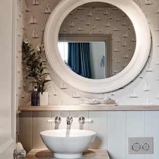 Cette image montre un WC et toilettes marin avec des portes de placard grises, un mur multicolore, une vasque, un plan de toilette en bois et un plan de toilette beige.